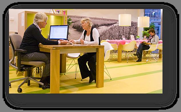 Zwei Menschen im Gespräch an einem Tisch mit Computerbildschirm  in offenem Raum