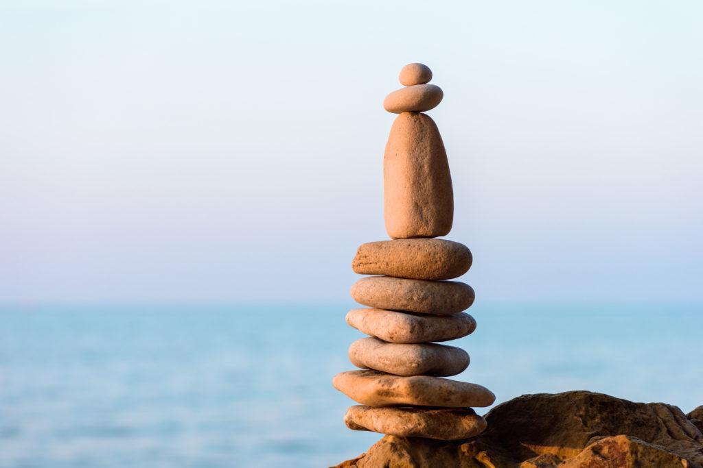 Steine balancieren aufeinander, im Hintergrund Meeresküste