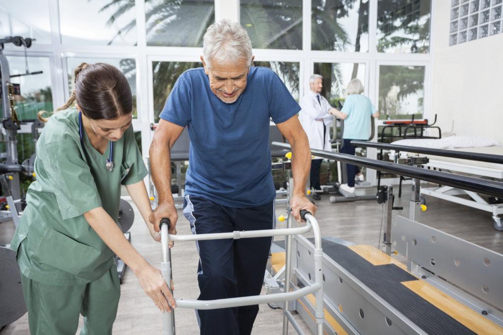 Junge Krankenschwester unterstützt einen älteren Mann der im Fitnessstudio der Reha gehen mit Gehhilfe übt.